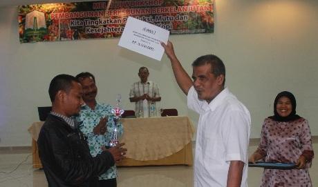 Penyerahan Hadiah oleh Ir. Nasrullah dari dinas perkebunan dan kehutanan Aceh kepada Idris Kasem Pemenang (I) kelompok tani berprestasi se Aceh (Foto Dok. ACDK)