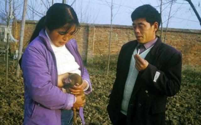 Jiao Xinzhen sedang menyusui seekor anak monyet disaksikan suaminya, Huang Aiqing