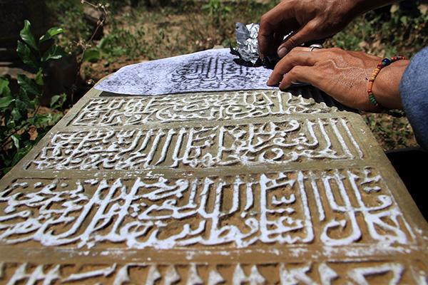Arkeolog Deddy Satria melakukan teknik rubbing pada Batu Nisan (Foto M Iqbal/SeputarAceh.com)