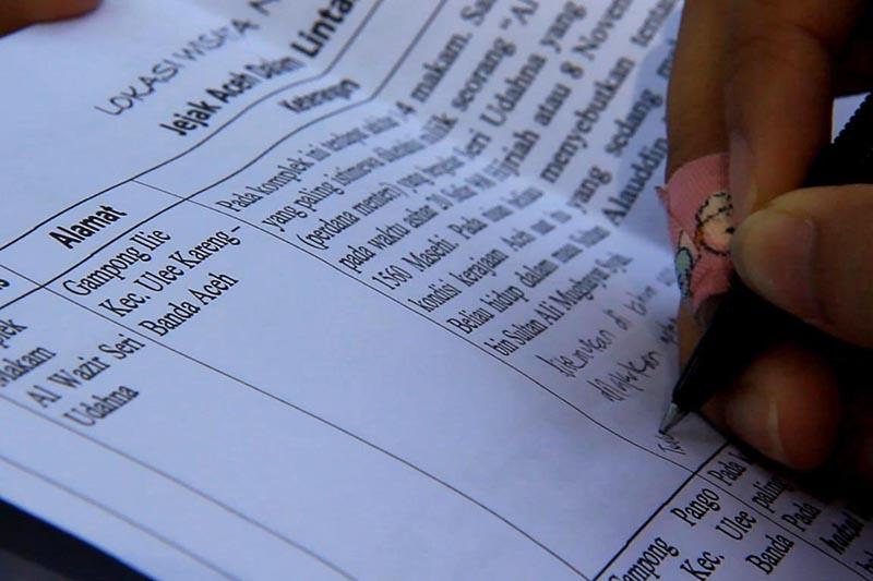Peserta napak tilas menulis informasi yang dijelaskan oleh arkeolog (Foto M Iqbal/SeputarAceh.com)