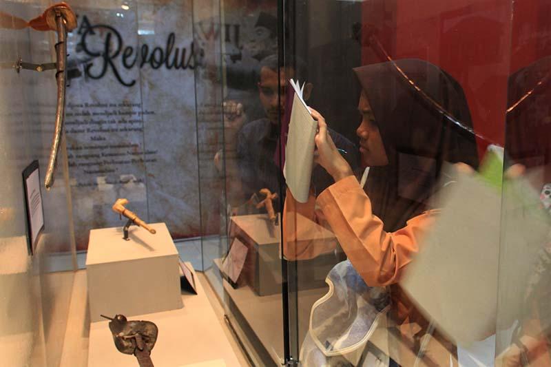 Siswa menulis informasi dari benda sejarah acara 100 tahun museum Aceh (Foto M Iqbal/SeputarAceh.com)