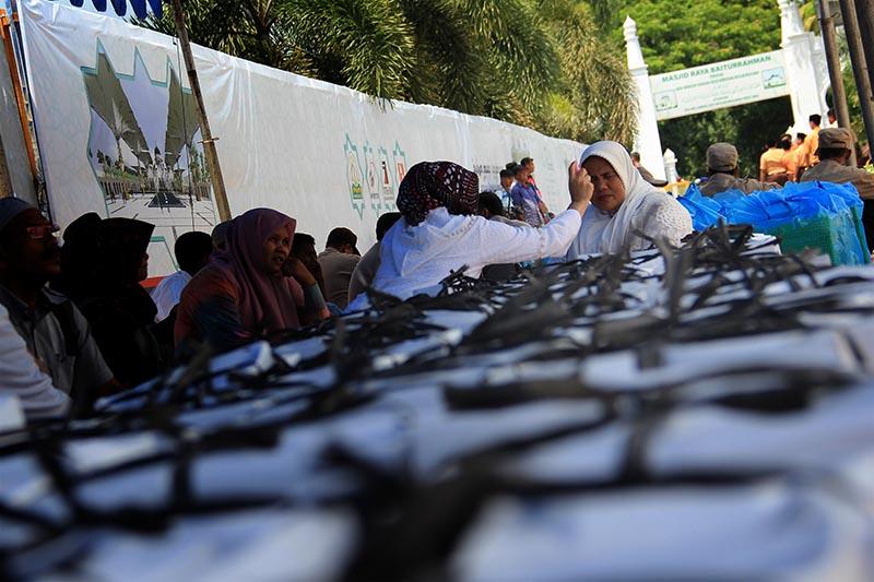 Seorang wanita menyemprotkan beauty water di bawah tenda nasi kotak acara 10 Tahun Perdamaian Aceh (Foto M Iqbal/SeputarAceh.com)