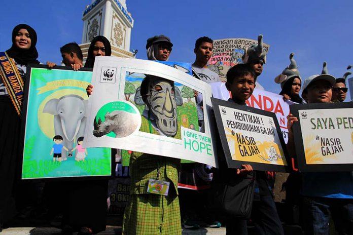 Sejumlah Komunitas dan anak-anak sekolah melakukan aksi Global Marching for Elephant, Rhino and Tiger di Simpang Lima, Banda Aceh. (Foto M Iqbal/SeputarAceh.com)