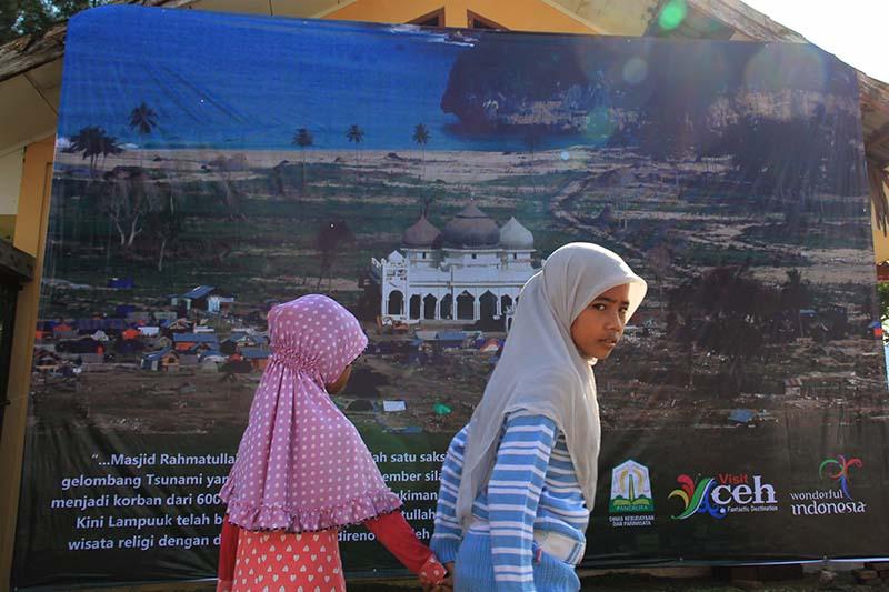 Anak-anak melewati baliho foto masjid Rahmatullah terkena dampak tsunami, Lampuuk, Aceh Besar (Foto M Iqbal/SeputarAceh.com)