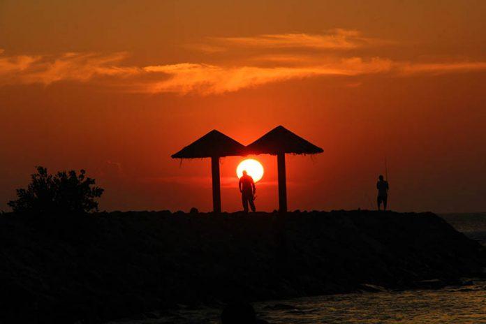 Pemancing berjalan melewati matahari, menjelang sunset di pantai Kuala Cut Lampuuk, Aceh Besar (Foto M Iqbal/SeputarAceh.com)
