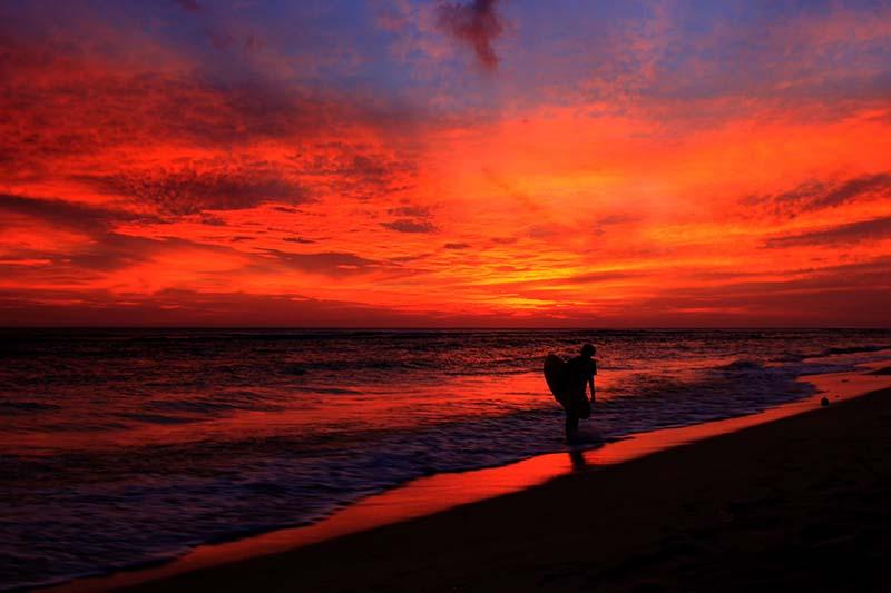 Surfer kembali ke pantai saat suasana sunset di pantai Kuala Cut Lampuuk, Aceh Besar (Foto M Iqbal/SeputarAceh.com)