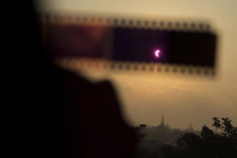 Melihat gerhana matahari menggunakan klise negatif film (Foto M Iqbal/SeputarAceh.com)