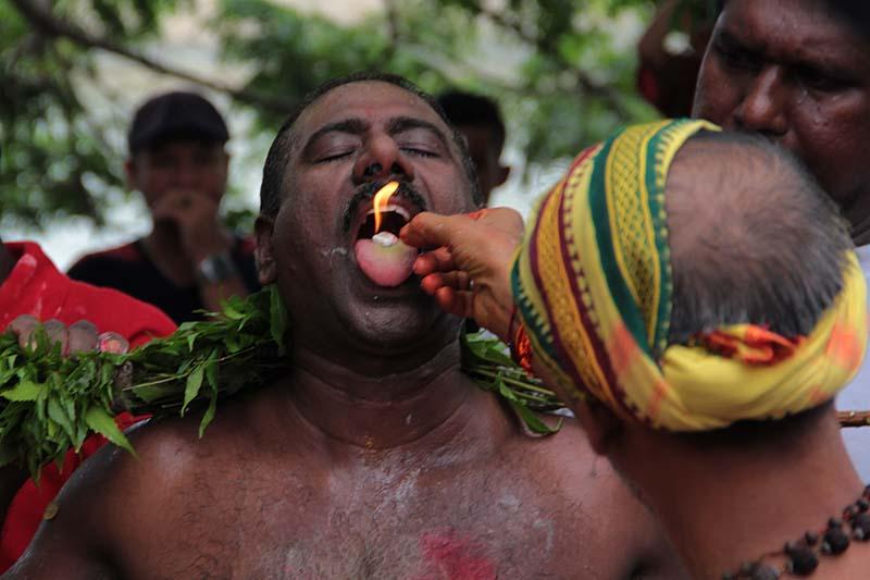 Gurukel Kuil Palani Andawer memasukkan unsur api kedalam mulut Pandita sebagai salah satu syarat medium masuknya kekuatan Dewa Murugan (Foto M Iqbal/SeputarAceh.com)