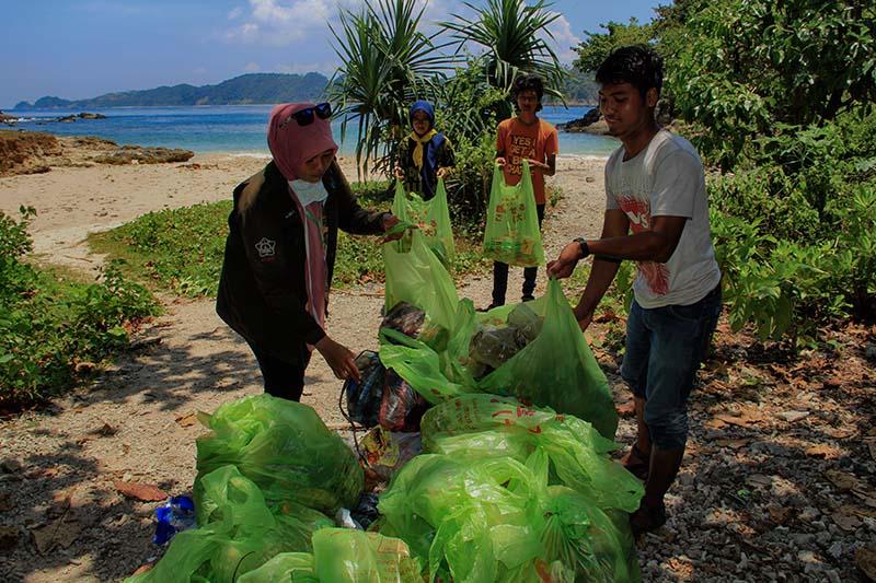 Mahasiswa Pertanian Caniva Unsyiah mengumpulkan sampah di pantai Lhok Mata Ie, Aceh Besar (Foto M Iqbal/SeputarAceh.com)
