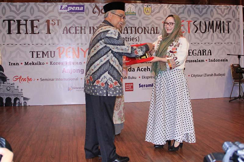 Gubernur Aceh Zaini Abdullah menyerahkan cinderamata kepada Atzimba Becerril (Meksiko) peserta acara Aceh International Poet Summit di Banda Aceh (Foto M Iqbal/SeputarAceh.com)