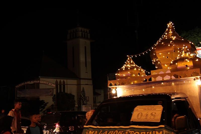 Peserta pawai takbir Idul Fitri membawa miniatur masjid melewati jalan di depan Gereja Hati Kudus Banda Aceh (Foto M Iqbal/SeputarAceh.com)