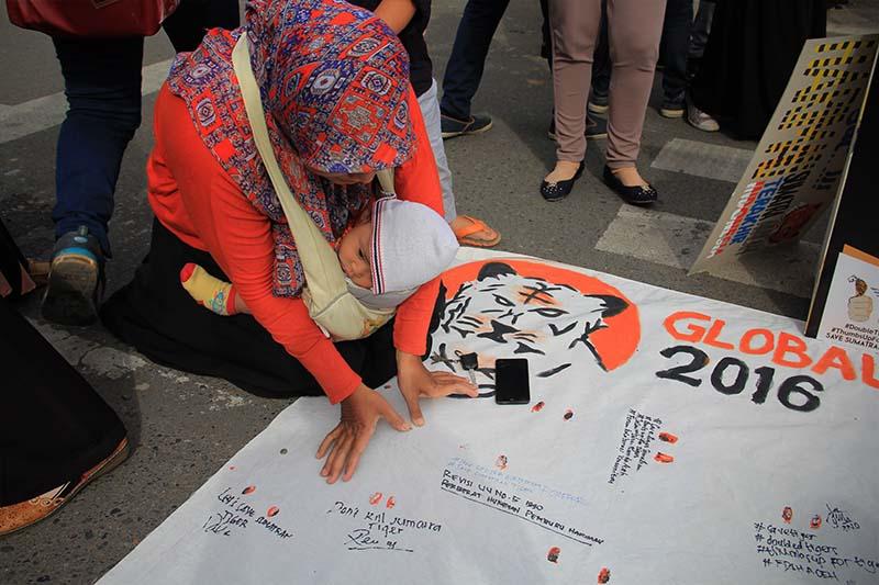 Seorang Ibu membubuhkan dua jempol ketika peringatan Hari Harimau Sedunia di Banda Aceh (Foto M Iqbal/SeputarAceh.com)